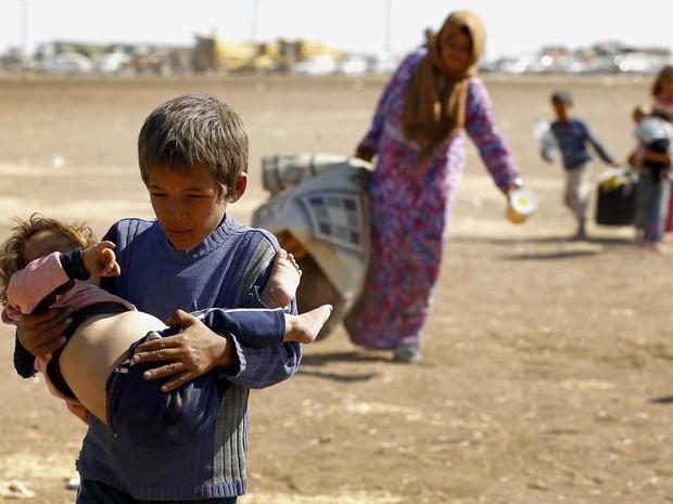 Jovem curdo sírio refugiado carrega uma criança após cruzar a fronteira entre a Síria e a Turquia, próximo a cidade turca de Suruç. Mais de 130 mil curdos sírios atravessaram a fronteira nos últimos 3 dias fugindo do avanço do grupo Estado Islâmico (Foto: Murad Sezer/Reuters)