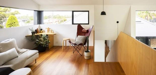 No andar de cima, uma pequena sala foi mobiliada com móveis modernos (Foto: Brett Boardman Photography)