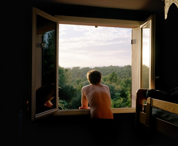 Bare chested man standing at open window, leaning on sill, rear view (Foto: Getty Images)