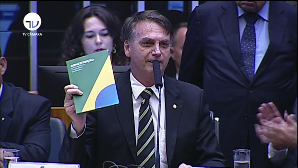 Bolsonaro mostra a Constituição durante cerimônia no Congresso — Foto: Reprodução/TV Câmara