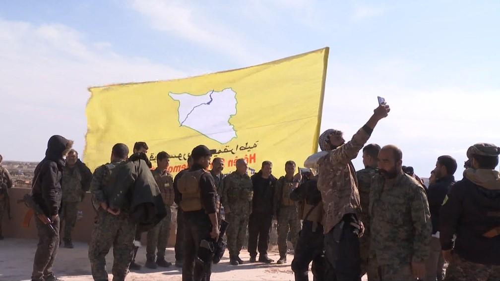 Membros das Forças Democráticas da Síria erguem sua bandeira no último reduto do Estado Islâmico em Baghuz, na Síria, neste sábado (23). — Foto: AFP