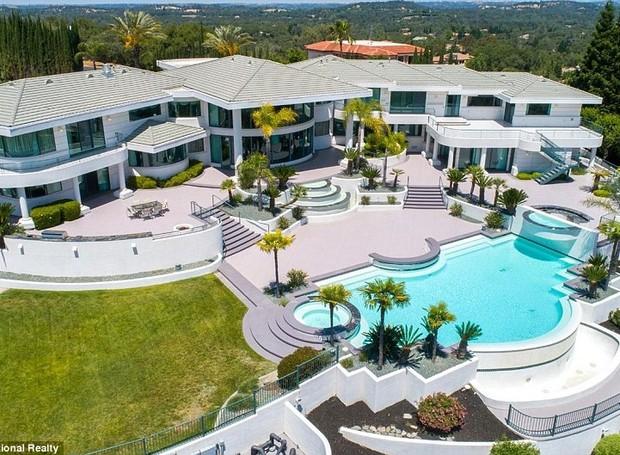 A parte de trás da casa é formada por gramados amplos e uma piscina cercada por palmeiras