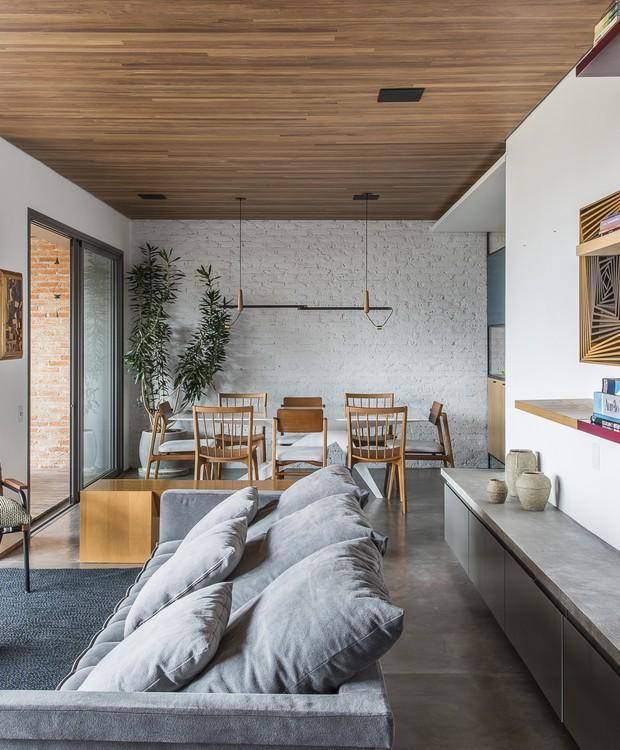 O forro de madeira no teto deixa os sons mais agradáveis na hora de ver TV. A mesa de centro com desenho do SuperLimão tem uma rede para as gatinhas da casa usarem na hora do cochilo  (Foto: Maira Acayaba/Divulgação)