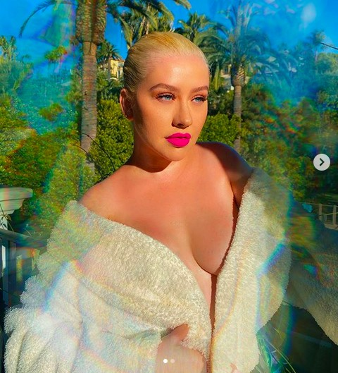 A cantora Christina Aguilera pegando um sol de roupão durante a quarentena (Foto: Instagram)