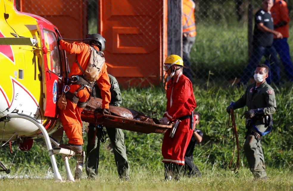 Equipe de resgate carrega corpo retirado da lama dois dias depois do rompimento da barragem da Vale, em Brumadinho. — Foto: Adriano Machado/Reuters
