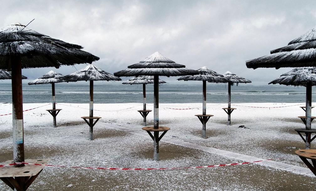 Neve cobriu barracas de quiosques em praia de Artemida, na Grécia — Foto: Vassilis Triandafyllou/Reuters