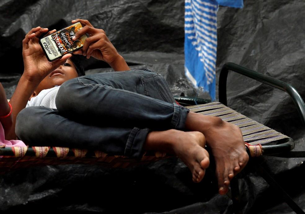 Um garoto assiste um filme em seu telefone celular enquanto deitado em uma maca na calçada em Kolkata, na Índia — Foto: Rupak De Chowdhuri/Reuters