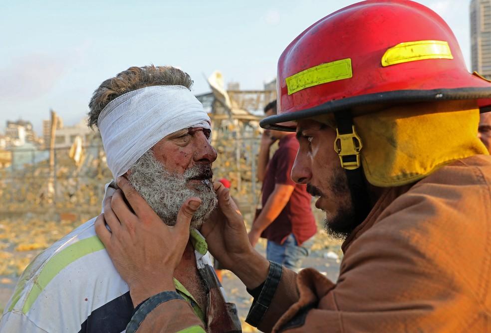 Homem ferido é examinado por um bombeiro perto do local de uma explosão em Beirute — Foto: Anwar Amro/AFP