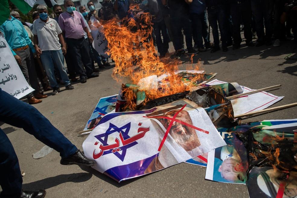 Palestinos queimam fotos do presidente dos EUA, Donald Trump, do premiê israelense Benjamin Netanyahu, do rei do Bahrein, Hamad bin Isa Al Khalifa, e do príncipe herdeiro de Abu Dhabi, Mohammed bin Zayed al-Nahyan, em protesto nesta terça-feira (15)  — Foto: Khalil Hamra/AP