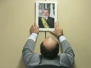 Líder do PR na Câmara, deputado Bernardo Santana, pendura na parede retrato oficial do ex-presidente Lula (Foto: Reprodução / GloboNews)