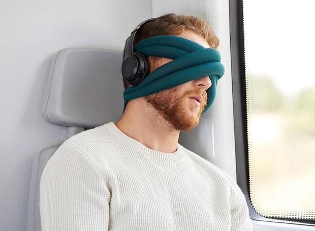 Há diversas versões de almofada. Nesse caso, um grande fio pode ser enrolado na cabeça, tapando os olhos e deixando a almofada para encosto ao lado das têmporas (Foto: Ostrichpillow/ Reprodução)