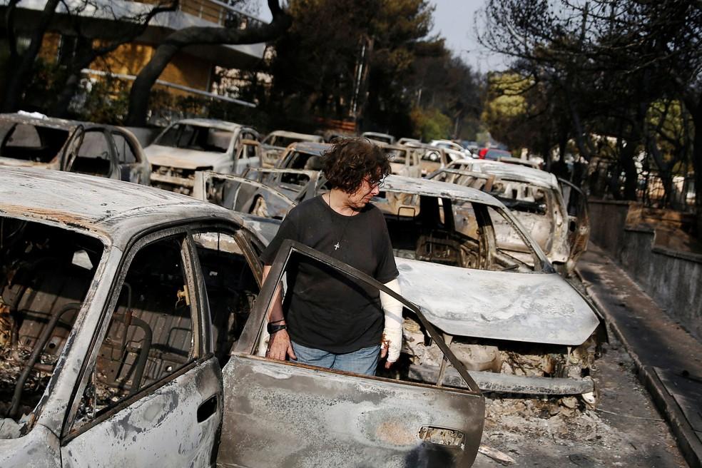 Mulher busca cachorro após incêndio que atingiu Mati, cidade perto de Atenas, nesta terça-feira (24)  (Foto: Costas Baltas/ Reuters)