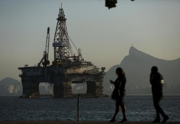 Pessoas passam por plataforma de petróleo em Niterói, no Rio de Janeiro - Brasil - Economia - Petróleo - produção - energia - Petrobras (Foto: Pilar Olivares/Reuters)