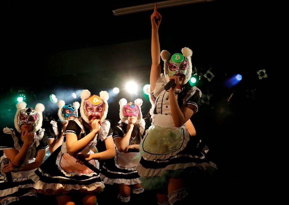 12 de janeiro - A banda Virtual Currency Girls (Garotas da Moeda Virtual) se apresentam com máscaras que levam na testa o símbolo de diferentes criptomoedas, como o Bitcoin e o Ripple, durante show de estreia em Tóquio (Foto: Kim Kyung-Hoon/Reuters)