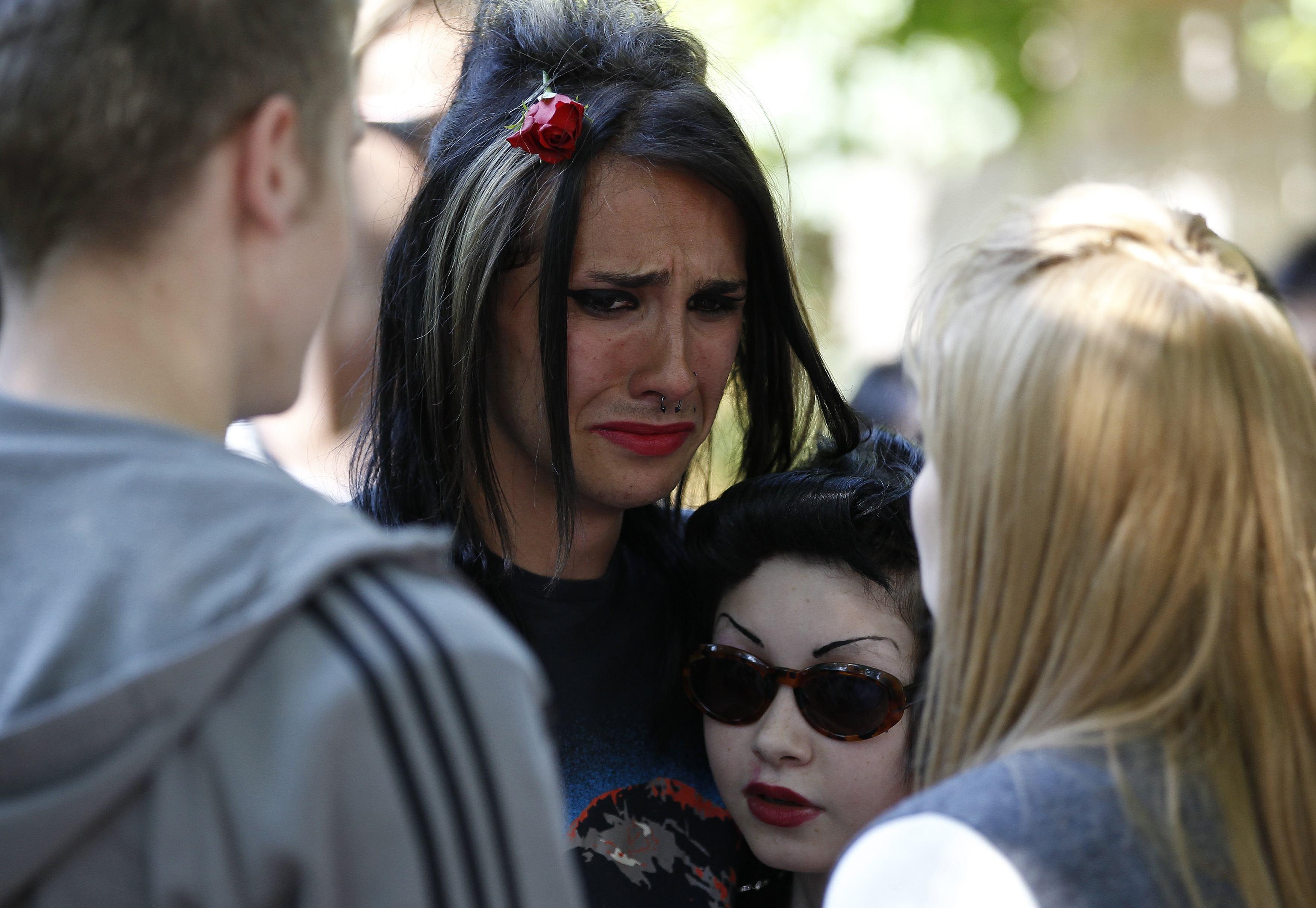 Os fãs reunidos, em comoção, do fora da casa de Amy Winehouse após sua morte, em 2011
