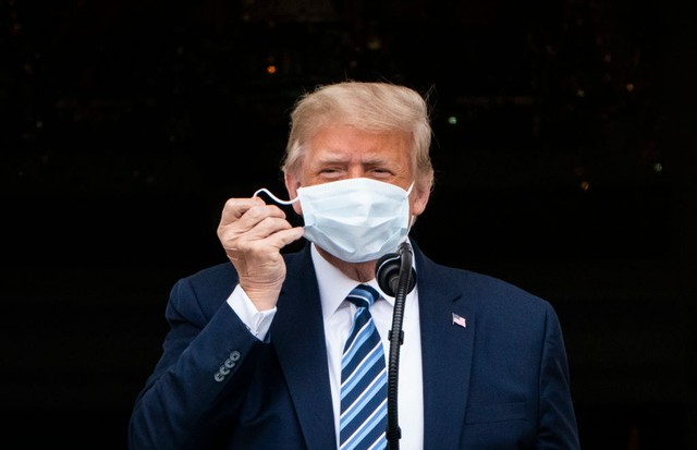 WASHINGTON, DC - OCTOBER 10: President Donald J. Trump, with a bandage in his hand, removes his face mask as he arrives to speak to supporters from the Blue Room balcony during an event at the White House on Saturday, Oct 10, 2020 in Washington, DC. Presi (Foto: The Washington Post via Getty Im)