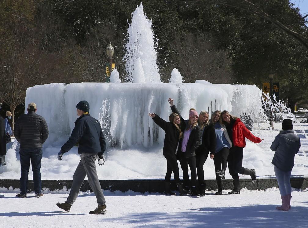 Estudantes da Universidade de Baylor tiram fotos diante de uma fonte congelada em Waco, Texas — Foto: Rod Aydelotte/Waco Tribune Herald via AP