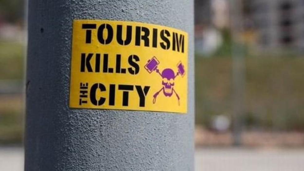 'O turismo mata a cidade', diz um adesivo colado em um poste, em Barcelona — Foto: Getty Images via BBC