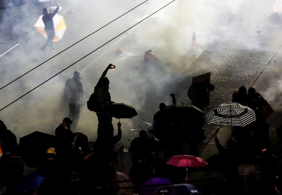 Manifestante registra ação da polícia que utilizou produtos químicos para dispersar ato contra o racismo em Seattle, nos Estados Unidos, nesta segunda-feira (8)  — Foto: Lindsey Wasson/ Reuters