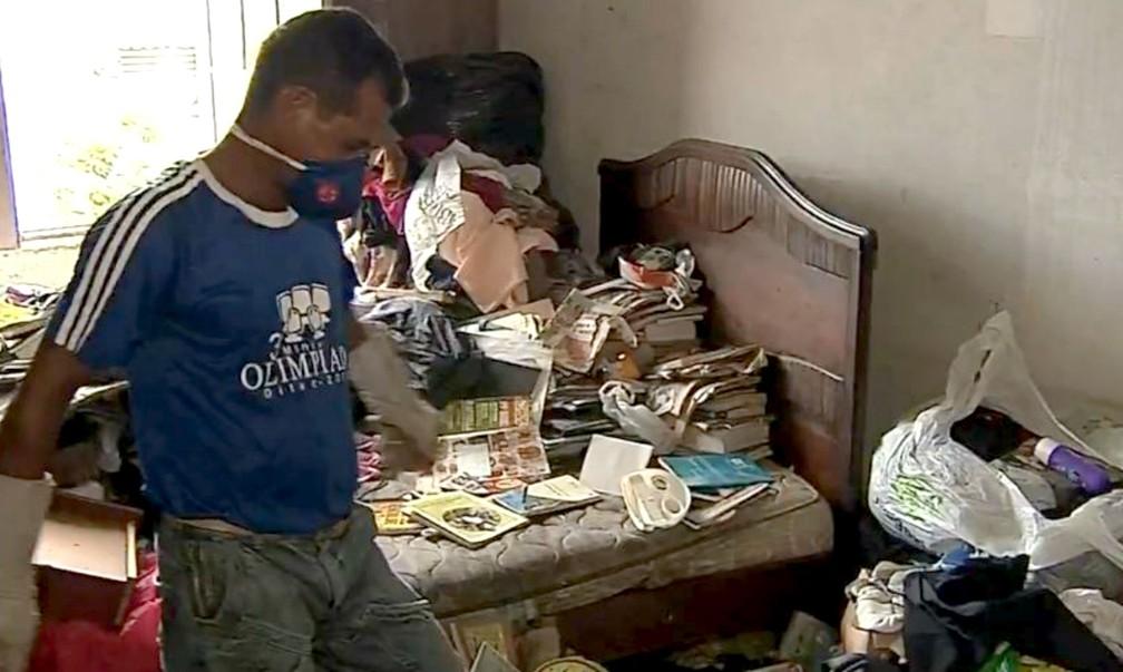 Funcionário da prefeitura protegido com luvas e máscaras: material está todo contaminado pela urina de ratos  — Foto: TV TEM/Reprodução