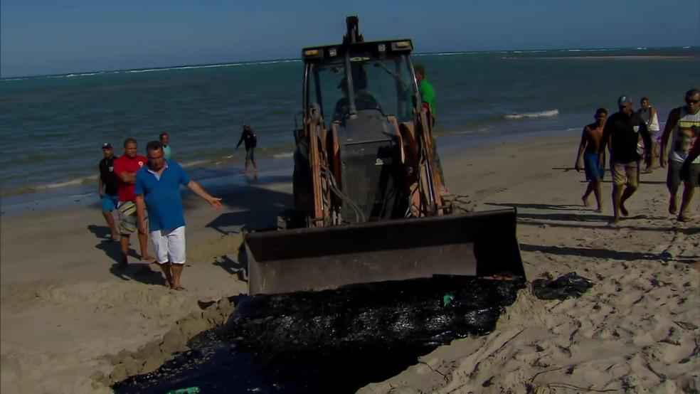 Trrator foi usado para retirar óleo que estava na areia em São José da Coroa Grande, no Litoral Sul de Pernambuco.  — Foto: Reprodução/TV Globo