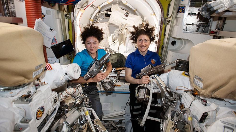 As astronautas da Nasa Jessica Meir (à esquerda) e Christina Koch dentro da câmara Quest, preparando os trajes espaciais e as ferramentas dos EUA que usarão na primeira caminhada 100% feminina no espaço — Foto: Nasa