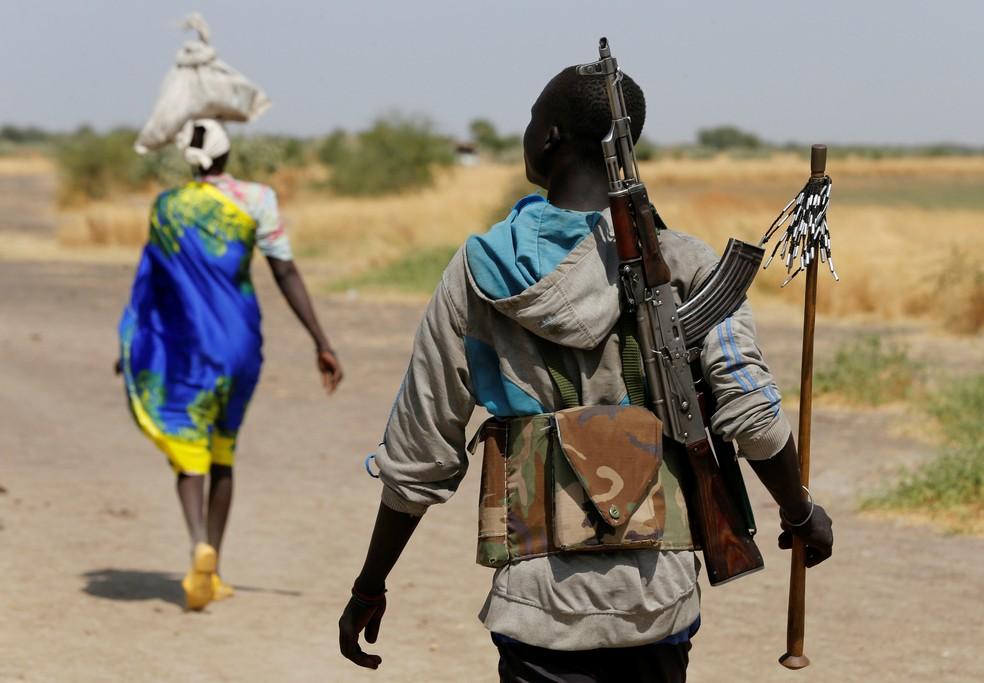 Homem armado anda perto da vila sul-sudanesa de Nialdhiu (Foto: Siegfried Modola/Reuters)