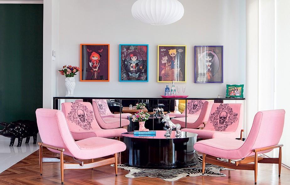 No espaço onde ficaria a mesa de jantar, a arquiteta Andrea Murao criou um lounge com mesa de centro baixa e aparador espelhado. Na parede, uma sequência de pôsteres
