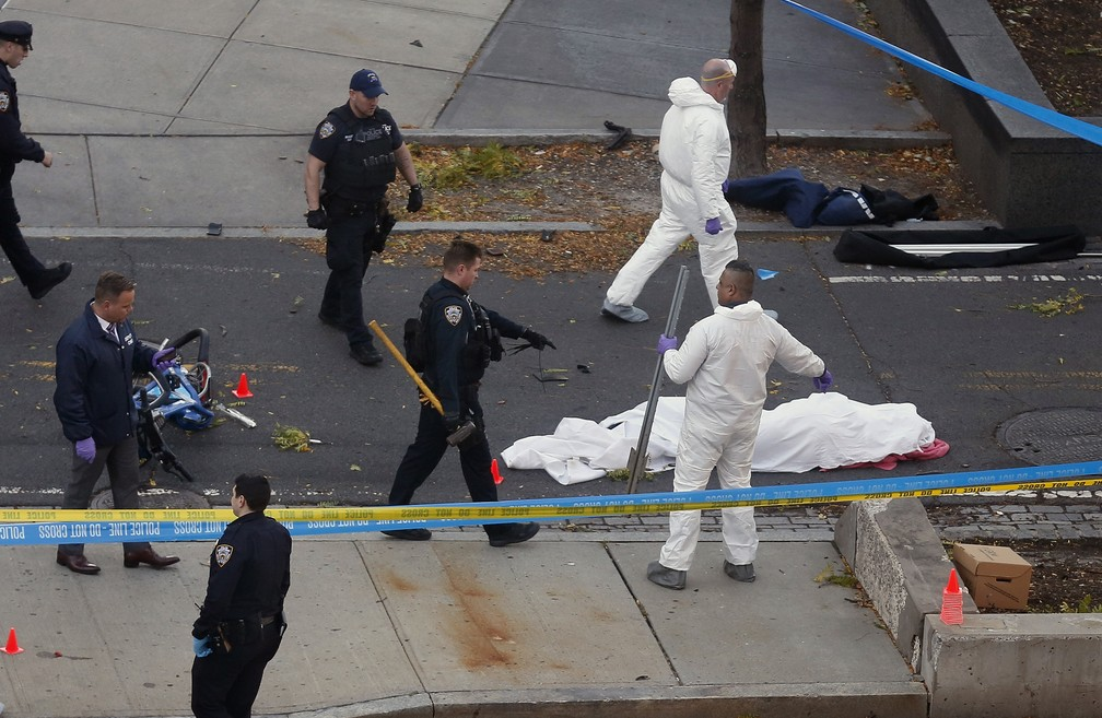 Autoridades investigam a cena perto de corpo coberto, em Nova York  (Foto: Bebeto Matthews/AP)