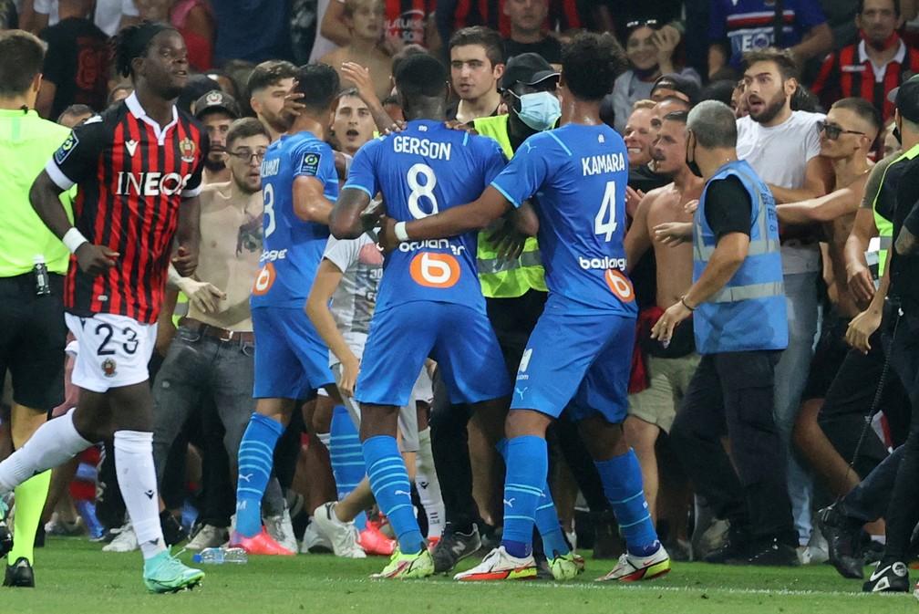 Gerson é contido por companheiros do Olympique de Marselha diante de torcedores do Nice que invadem o gramado — Foto: Valery HACHE / AFP