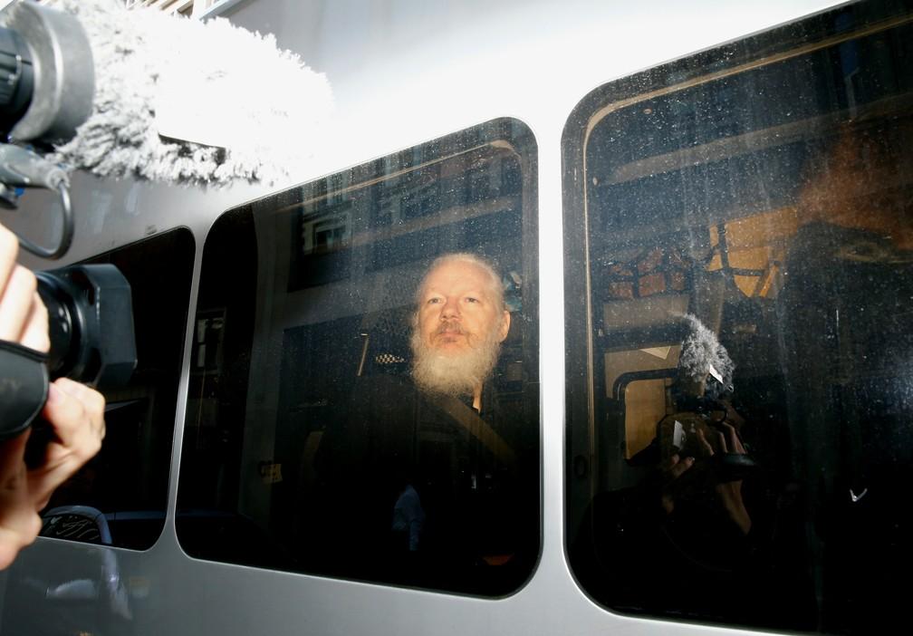 O fundador do WikiLeaks, Julian Assange, dentro de van da polícia que o levou ao Tribunal de Magistrados de Westminster, depois de ser preso em Londres, em abril — Foto: Hannah McKay/Reuters