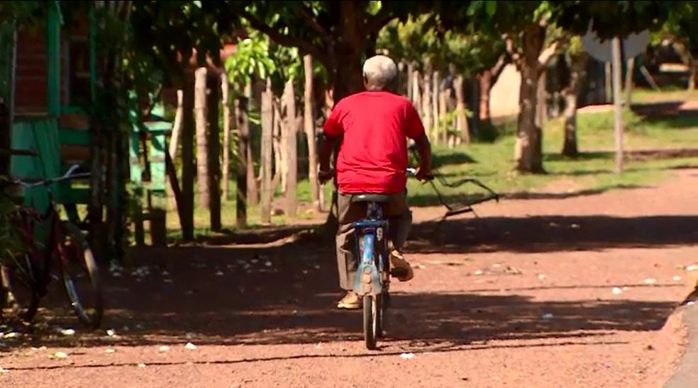 Sebastião distribui o jornal pela comunidade de bicicleta (Foto: Rede Amazônica/Reprodução)