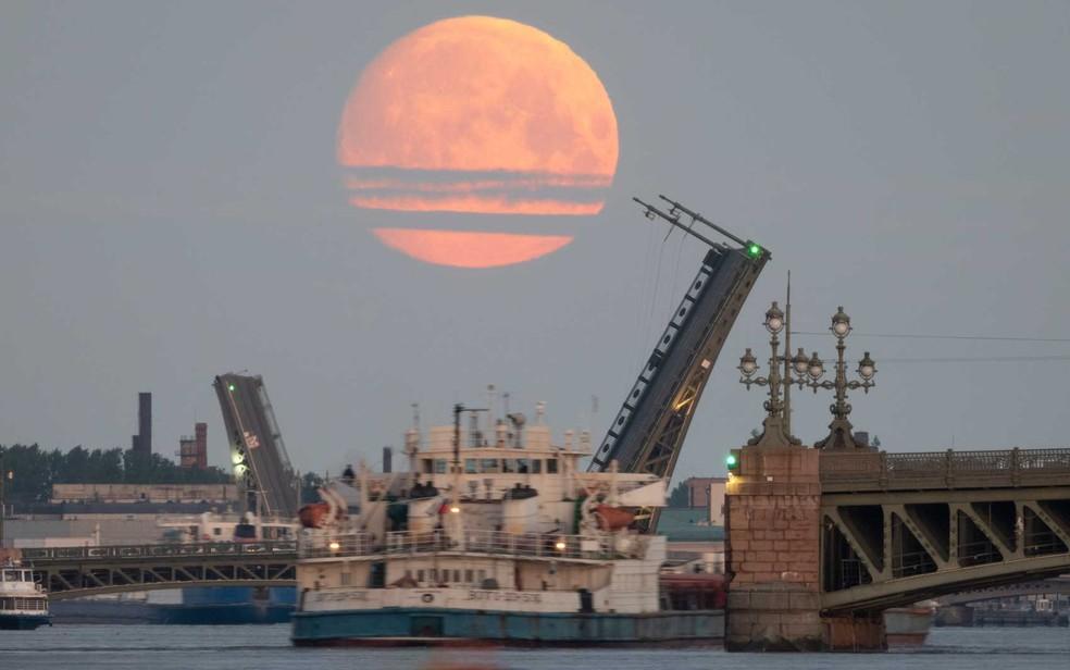 Pontes levadiças se erguem no rio Neva, com a lua no céu, em São Petersburgo, Rússia — Foto: Dmitri Lovetsky / AP Photo