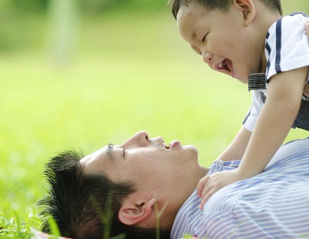 Pai brincando com filho na grama (Foto: Shutterstock)