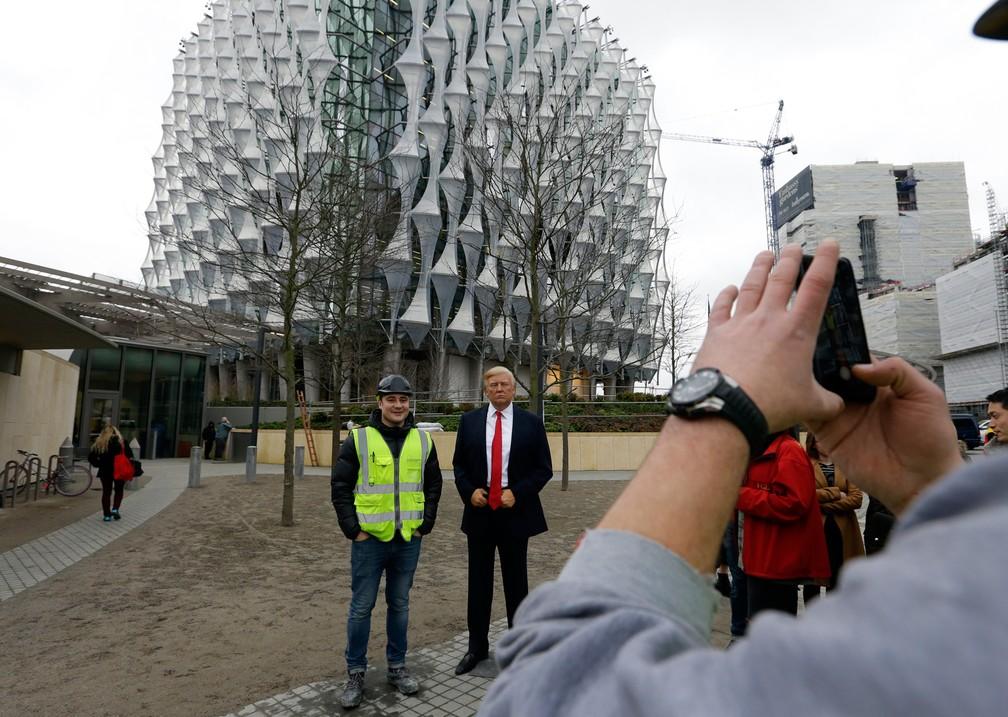 12 de janeiro - Homem posa para foto ao lado de estátua de cera do presidente Donald Trump, colocada na frente da nova embaixada americana em Londres após ele criticar a escolha do local, feita durante o governo Obama (Foto: Alastair Grant/AP)