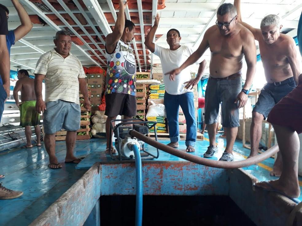 Bomba de sucção foi usada para retirar a água que entrava no barco (Foto: Geovane Brito/G1)