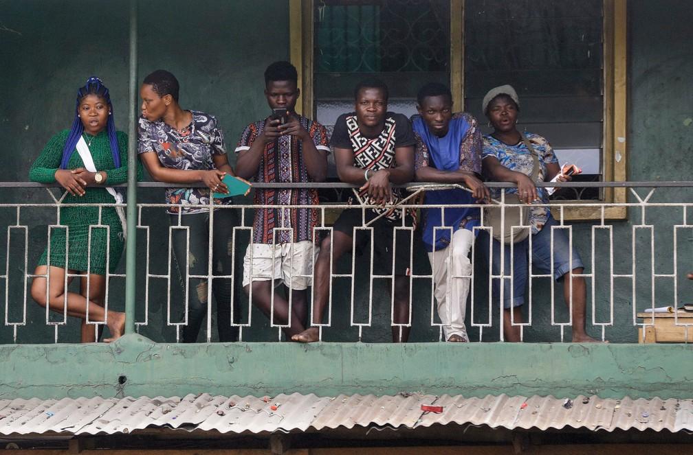 Moradores de um prédio olham da varanda em Lagos, na Nigéria, durante isolamento para evitar a propagação do novo coronavírus — Foto: Sunday Alamba/AP