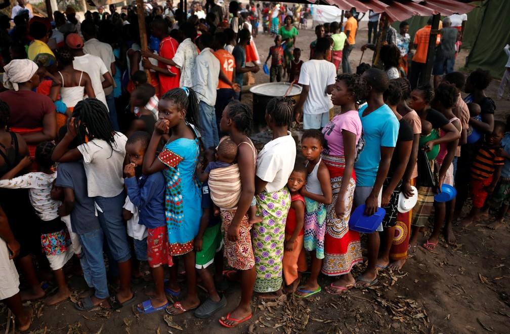 Pessoas esperam em fila por comida em um campo para desabrigados depois do ciclone Idai, na Beira, em Moçambique, nesta terça (26). — Foto: Reuters/Mike Hutchings