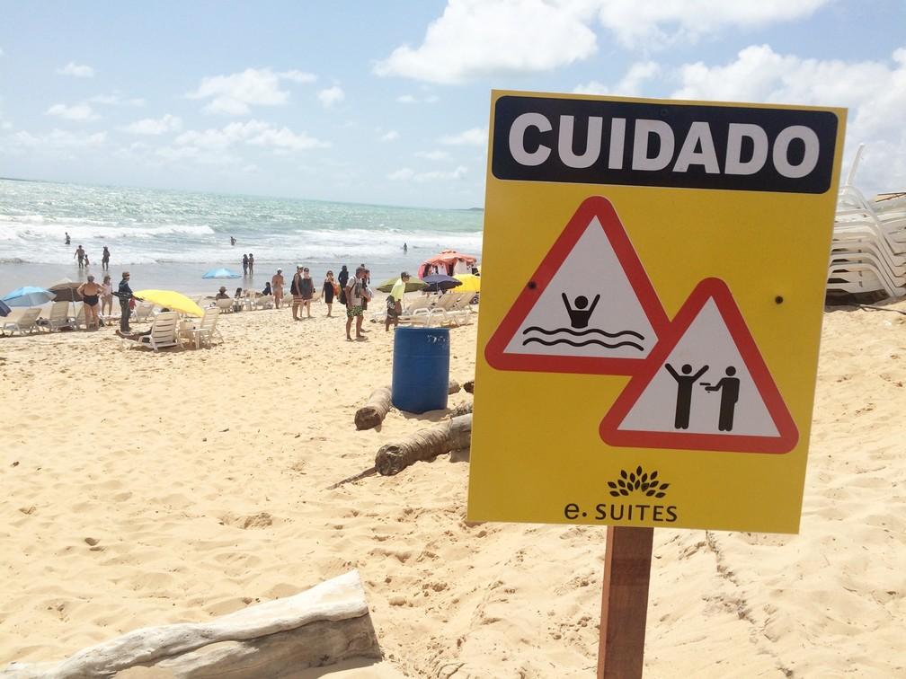 Na areia da praia, hotel fincou placas para alertar os hóspedes. É preciso atenção com os riscos de afogamento e de assaltos  (Foto: Anderson Barbosa/G1)