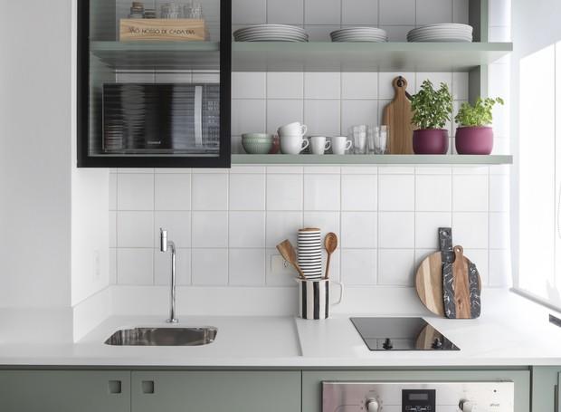 A cozinha é pequena, mas completa. Cooktop, forno e microondas dividem espaço com as prateleiras suspensas e seu vitrô móvel. Na parte de baixo, um armário guarda os utensílios do dia a dia  (Foto: Evelyn Müller/Divulgação )