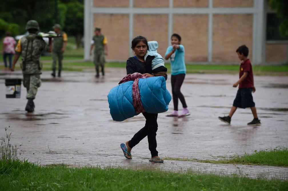 Mulher carrega bebê e seus pertences até abrigo em Escuinapa, em Sinaloa, no México, na terça-feira (23)  — Foto: Alfredo Estrella / AFP