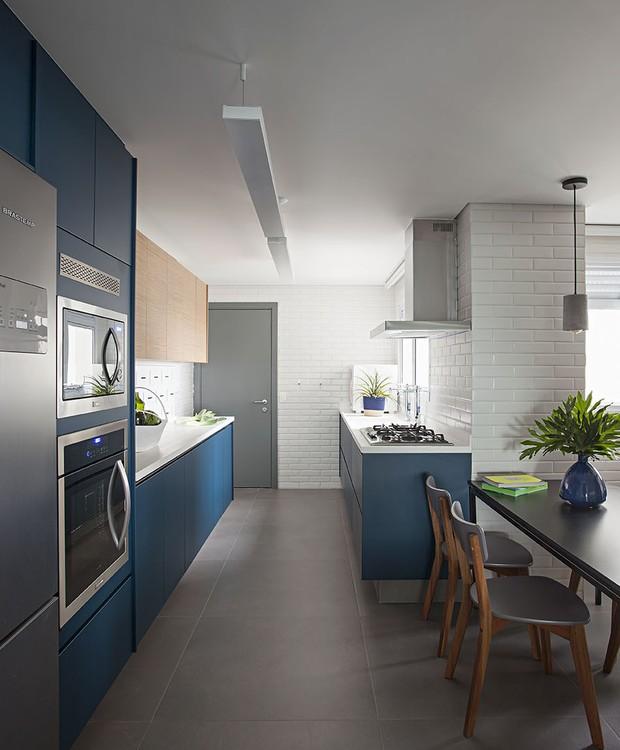Bem distribuída em seu formato de corredor, a cozinha mantém o foco na praticidade com acabamentos fáceis de manter (Foto: Gui Morelli/Divulgação Produção: Núria Uliana)