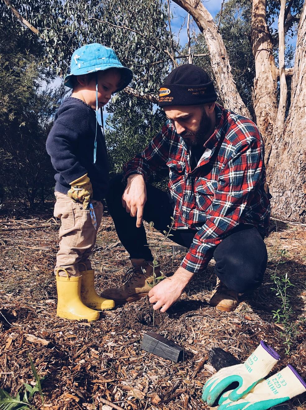 """Pai e filho plantando árvores: """"germinar uma semente com seu filho ou observar a fase de uma árvore em sua rua é um bom exercício"""", diz especialista. — Foto: Crema Joe/Unplash"""