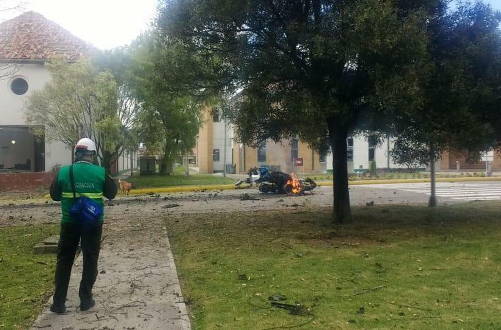 Carro em chamas é visto em academia da polícia colombiana nesta quinta-feira (17) em Bogotá — Foto: AP Photo