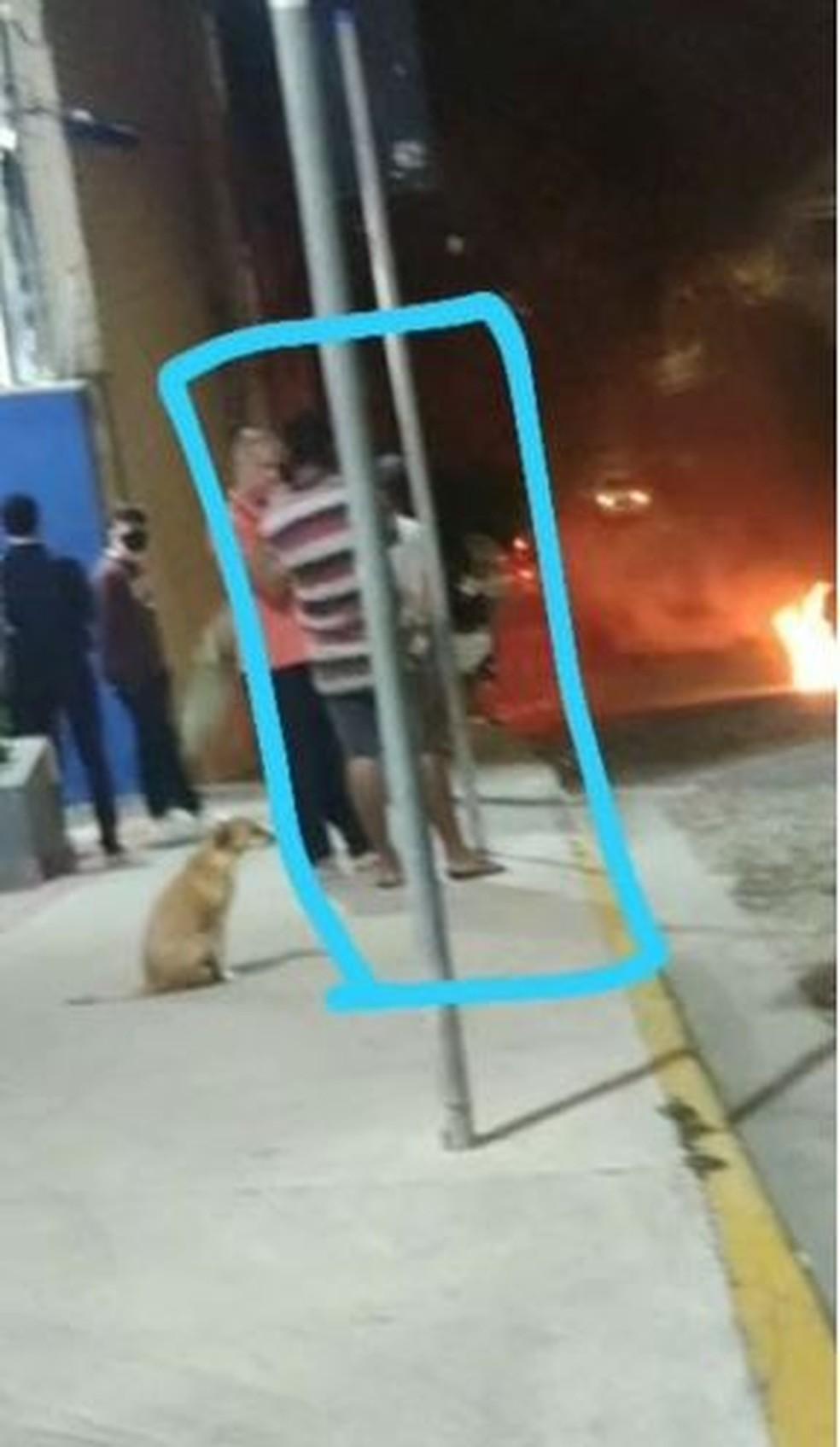 Suspeito, de camisa listrada, acompanhado de cachorro, observa carro incendiado — Foto: Redes sociais