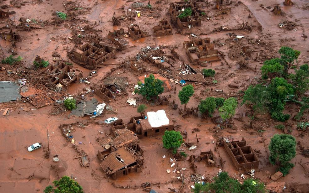 06/11 - Carros e destroços de casas são vistos em meio a lama após o rompimento de uma barragem de rejeitos da mineradora Samarco no Distrito de Bento Rodrigues, no interior de Minas Gerais — Foto: Christophe Simon/AFP