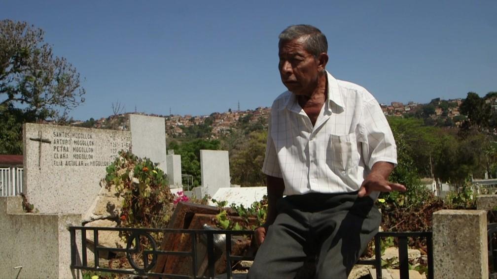 Eladio Batisda diz que vigia o túmulo da mulher em cemitério da Venezuela para evitar ação de vândalos — Foto: BBC