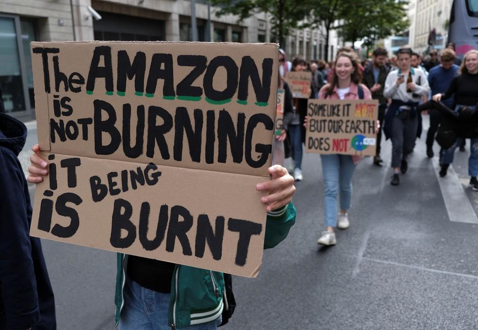 Greve pelo Clima: Na Alemanha, manifestante segura cartaz com frase sobre a Amazônia: 'A Amazônia não está queimando, está sendo queimada'. O protesto ocorre nesta sexta, 20 de setembro. — Foto: Wolfgang Rattay/Reuters