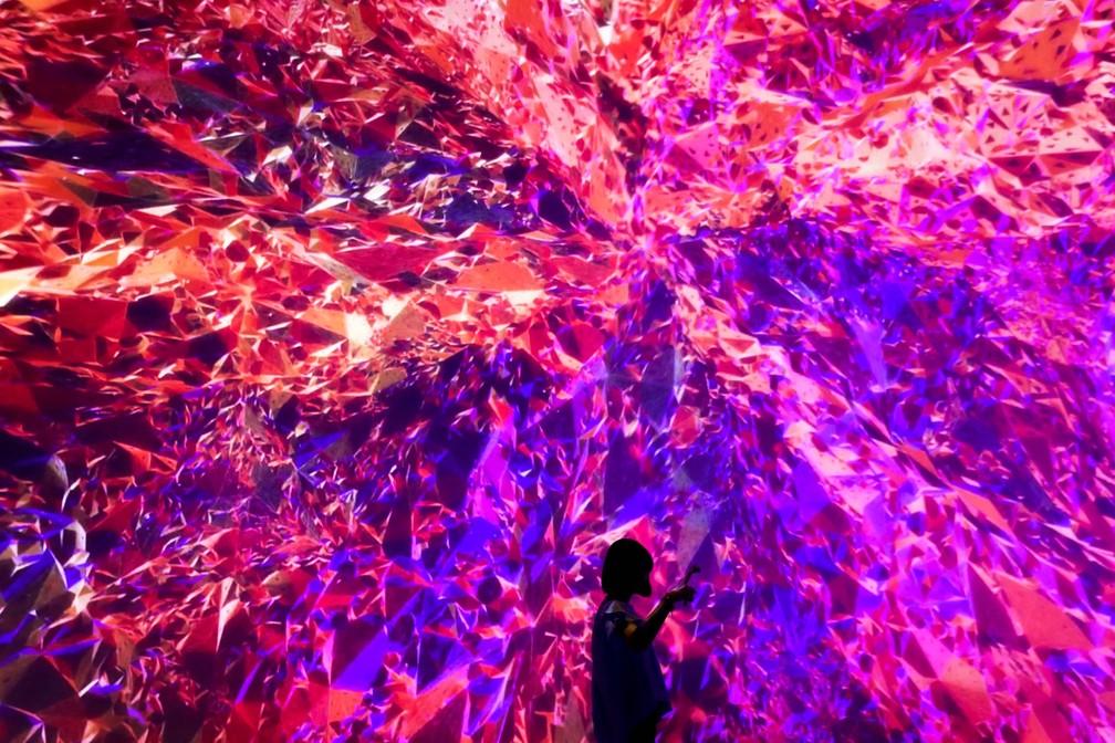 Mulher tira um selfie diante da instalação audiovisual intitulada 'Cornerstone' ('Pedra Angular', em inglês), que faz parte da mostra O Futuro de Hoje no Museu Today Art em Pequim, na China (Foto: Andy Wong/AP)