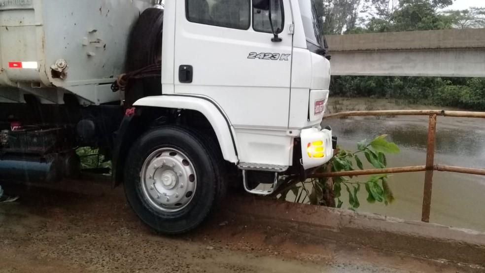 Caminhão ficou com uma das rodas penduras e quase caiu dentro do rio — Foto: Reprodução/WhatsApp